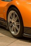 Expensive orange super car front tire. On concrete paving Stock Photos