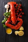 Expensive organic food: boiled lobster with lemon, garlic, fresh. Tomatoes and herbs close-up on a black table. Vertical top view from above stock photos