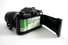 Expensive Photography. 35mm camera with money representing film royalty free stock photo