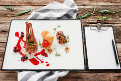 Expensive restaurant meal with blank notepad. Grilled ribs with vegetables and cherry sauce. Degustation, luxury lifestyle, choosing menu for party concept stock images
