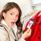 Expensive shopping prices. In euro. Woman shopper shocked and surprised over high clothes retail prices in clothing store. Funny image of multicultural young stock image