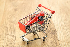 Expensive sports car in a shopping cart. A conceptual image of an expensive sports car in a supermarket shopping cart Stock Photo