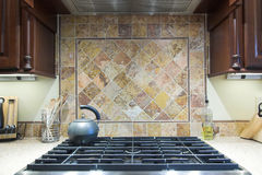 Expensive stove and backsplash. Expensive industrial cooktop with tile backsplash royalty free stock images