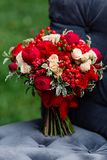 Expensive, trendy wedding bouquet of roses in marsala and red colors standing on chair. Bridal details and decor with flowers.  Royalty Free Stock Photos