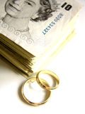 Expensive Wedding. Two wedding rings (bands) next to a pile of ten pounds bills with England's Queen image
