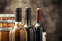 Expensive wine collection. Expensive wine bottles collection and wooden barrel in the cellar, wine tasting and production concept royalty free stock photography
