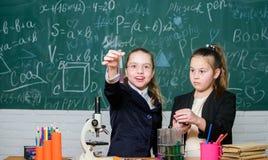 experiências da ciência no laboratório de química Pesquisa da química Pouco trabalho do cientista com microscópio Meninas dentro fotos de stock royalty free