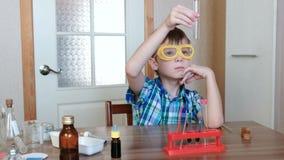 Experiências na química em casa O menino está olhando o tubo para certificar-se d o ` s limpo filme