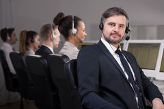 Experience and professionalism of consultant. Male consultant confidently is sitting on a chair and waiting for next call. His co-workers are sitting behind him Stock Images