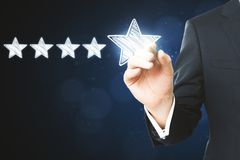 Experience rating and quality concept. Businessman pointing at abstract stars on blurry blue background. Experience rating and quality concept stock photography