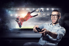 Experience the reality of game. Mixed media. Emotional guy wearing glasses playing gamepad. Mixed media Stock Image