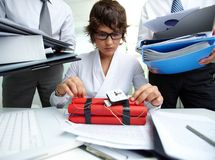 Experienced accountant. Serious secretary with dynamite being surrounded by big heaps of papers held by men stock images