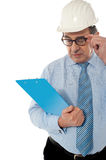 Experienced achitect in hardhat studying files. Royalty Free Stock Photography