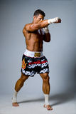 Experienced adult fighter punches during training. Kickboxing Stock Photo