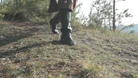Experienced archer walking along on grass in summer afternoon. Bowman in leather boots and national clothes is going forward confidently on verdant grass in stock video footage