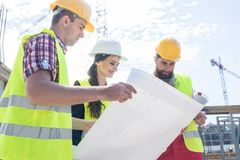Experienced architect analyzing a blueprint on the construction site. Experienced female architect smiling while analyzing a blueprint together with two workers royalty free stock photos