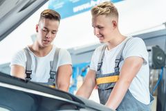 Experienced auto mechanic checking the parts of a car in a moder Royalty Free Stock Photos