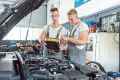 Experienced auto mechanic using a laptop for scanning engine err Royalty Free Stock Photos