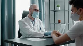 Experienced bald doctor in disposable face mask and glasses