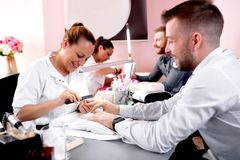 Experienced beauty salon worker handling her customer with a manicure treatment. Nail treatment royalty free stock photography
