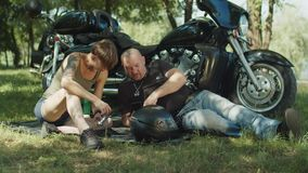 Experienced biker showing on phone tool for repair. Handsome biker using cellphone while helping stylish woman to choose right wrench for motorbike repair stock footage