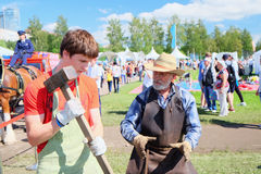 Experienced blacksmith teaches the craft of a young man at the festival Royalty Free Stock Photography