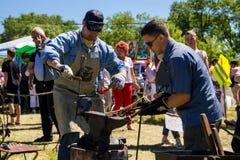 Experienced blacksmith teaches the craft of a young man Stock Photos