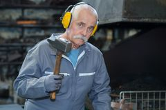 Experienced blacksmith using hammer in workshop Stock Photography