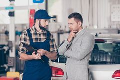 Experienced brunet bearded expert specialist in blue overall is. Discussing and demonstrates the demages of businessman`s car, he is ponder pensive, focused and stock photography