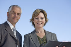 Experienced business couple on location. With the woman holding an agenda Royalty Free Stock Images