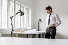 Experienced businessman analyzing important blueprints. Standing at white desk in the office royalty free stock image