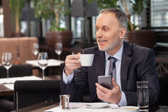 Experienced businessman is enjoying hot drink in cafe Stock Photos