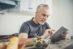 Experienced businessman having dinner at home. Dinner at home. Experienced handsome businessman reading article on his tablet while having dinner at home stock photo
