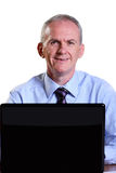 Experienced businessman looking up fom his laptop Royalty Free Stock Photos