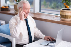 Experienced businessman talking on his cellphone. We need to talk about that. Smiling grey haired mature man discussing something with his partner during a phone Royalty Free Stock Photo