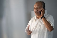 A experienced businessman talking by phone using a smartphone to two way communication. Although far away royalty free stock image