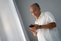 A experienced businessman using a smartphone to control his business from far places. When he stay at home stock images