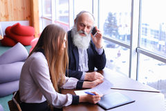 Experienced businessmen retired takes call on phone and shares a Royalty Free Stock Photography