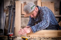 Experienced carpenter. In work clothes and small buiness owner measures a wooden board with a ruler and marks with pencil the necessary points for slices royalty free stock photography