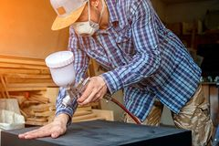 Experienced carpenter. In work clothes and small buiness owner paints a wooden box from the dresser in black color in workshop, in the background a lot of tools stock photo