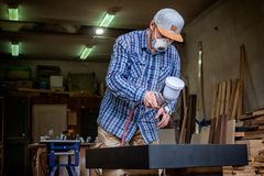 Experienced carpenter. In work clothes and small buiness owner paints a wooden box from the dresser in black color in workshop, in the background a lot of tools royalty free stock photography