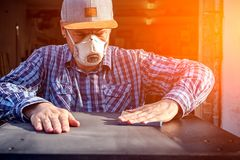 Experienced carpenter. In work clothes and small business owner working in woodwork workshop, using sandpaper for polishing wooden at worktable in workshop royalty free stock photos