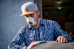 Experienced carpenter. In work clothes and small business owner working in woodwork workshop, using sandpaper for polishing wooden at worktable in workshop stock photos