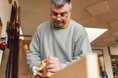 Experienced carpenter planing a board stock photo