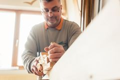 Experienced carpenter planing wood in workshop royalty free stock image