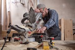 Close up circular saw. Experienced carpenter in work clothes and small buiness owner working in woodwork workshop, using a circular saw to cut through a wooden Royalty Free Stock Images