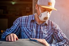 Experienced carpenter. In work clothes and small business owner working in woodwork workshop, using sandpaper for polishing wooden at worktable in workshop royalty free stock image