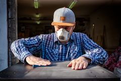 Experienced carpenter. In work clothes and small business owner working in woodwork workshop, using sandpaper for polishing wooden at worktable in workshop stock image