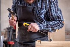 Experienced carpenter work with wooden. Close up experienced carpenter in work clothes and small buiness owner working in woodwork workshop, using chisel for stock image