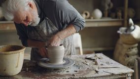Experienced ceramist grey-haired bearded man is smoothing molded ceramic pot with wet sponge. Spinning throwing wheel. Muddy work table and handmade clayware stock video